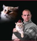 A classic, there's too much to love about this picture: the mid-90's snowflake sweater, the exact same facial expression being shared by both pet and owner, the miniature Santa hat. But the best part of all is clearly the huge cat head floating around to the left.