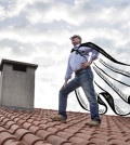 Superdad standing on roof with billowing cape